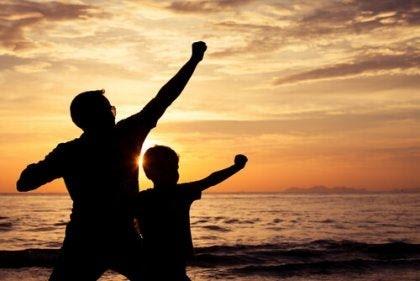 Padre e hijo jugando al atardecer a ser héroes